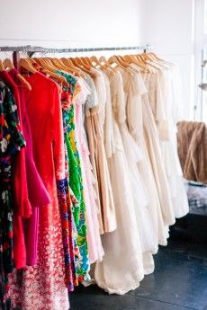 A glowing rack of vintage designer dresses, wedding gowns and bridesmaids dresses at Dolly Up Vintage Emporium photographed by Kiss and Tell Photography
