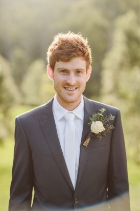 Groom in grey suit with white tie