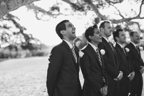 groom laughing as he sees his bride