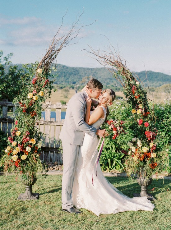 Bride and groom with floral arch