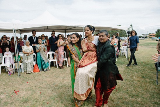 Bride being carried down the aisle at Indian wedding