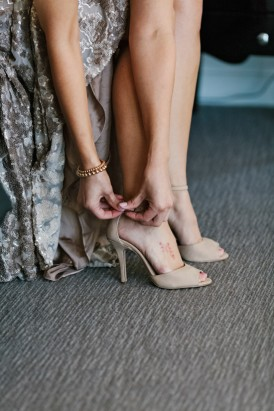 Bride doing up taupe shoes