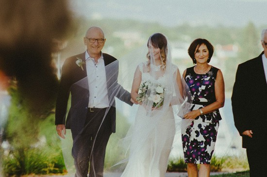 Bride walking down aisle with aprents