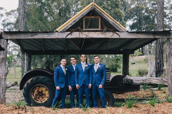 Groom and groomsmen in front of tractor