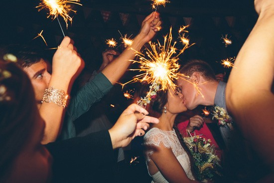 Kissing with sparklers at wedding