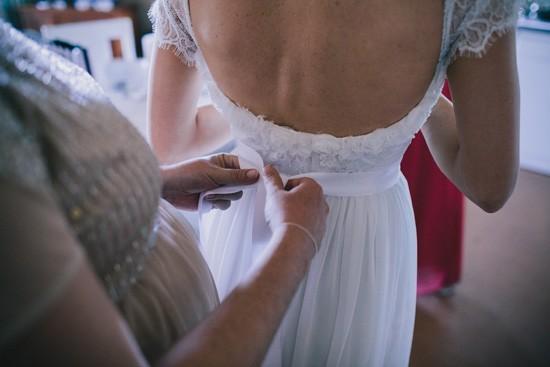Tying bow on brides dress