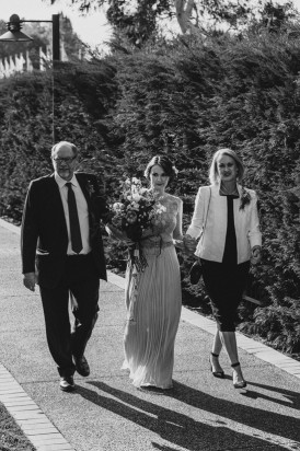 Bride walking with parents