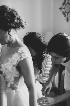 Buttoning brides wedding dress
