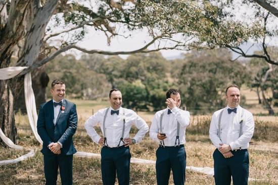 Groom in suit with groomsmen in braces