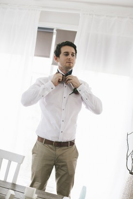 Groom in taupe pants and white shirt