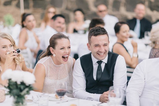Newlyweds laughing at wedding speeches