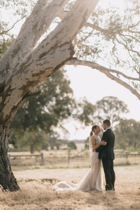 Newlyweds under tree in country