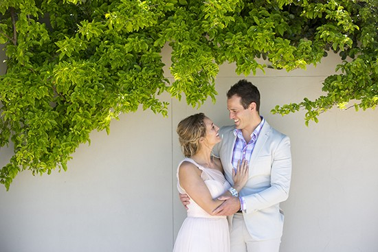 Engagement Photo againats a wall with green trees