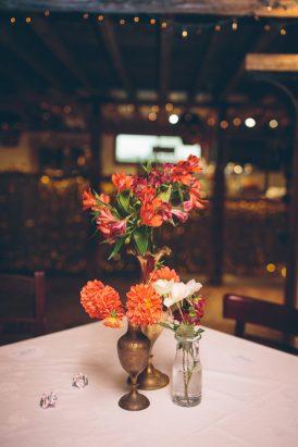 Orange flowers in brass vases